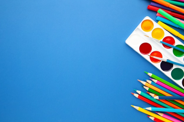 Watercolor paints, pencils and brushes on blue. creative artistic mockup with copyspace.