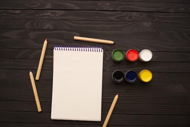 Watercolor paints pencils notepad drawing tools art dark wood background