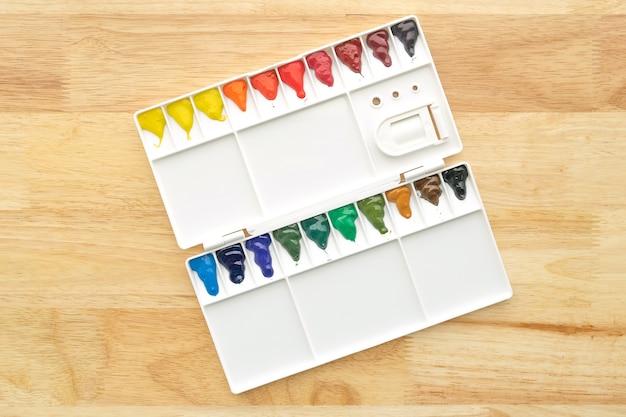 Набор акварельных красок. цвет в акварельной палитре с деревянным фоном. яркие разноцветные акварельные краски в коробке для краски.