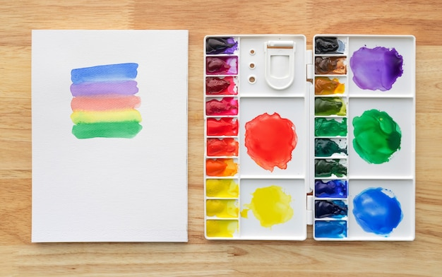 Watercolor paints set in white palette with white paper background. colorful multicolored aquarelle paints in paint box.