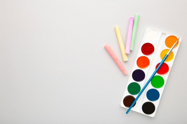 Watercolor paints set with brushes and crayons for drawing on grey background