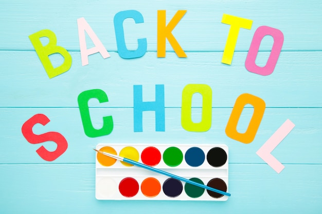 Watercolor paints set with inscription back to school on blue background