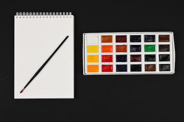 Акварельные краски с кистью на черном столе. палитра разноцветных красок для рисования.