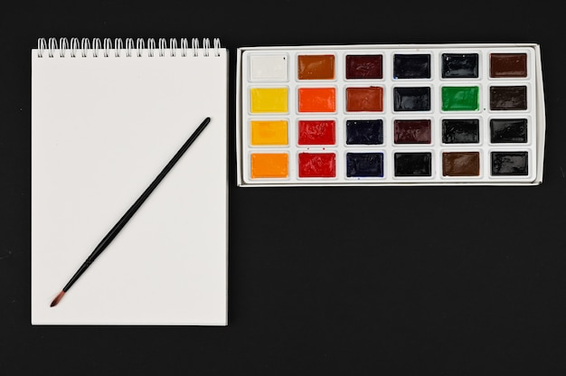블랙 테이블에 브러시로 수채화 물감입니다. 그리기위한 다색 페인트 팔레트입니다.