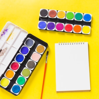 Colori ad acquerello con blocco note sul tavolo