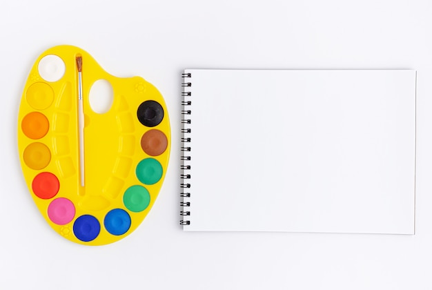 Watercolor palette and scetchbook blank on white background. flat lay, mockup.