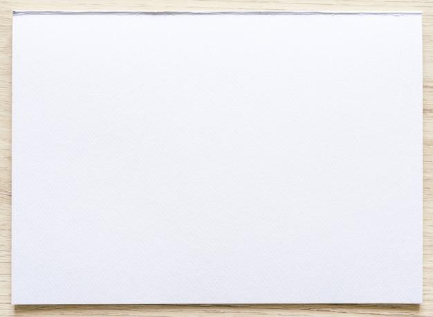 Текстура акварельной бумаги на деревянной предпосылке с путем клиппирования. лист белой бумаги с рваными краями. художественная бумага с текстурой высокого качества в высоком разрешении.