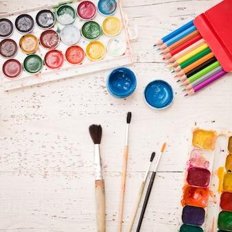 白い木製のテーブルに水彩絵の具、ブラシ、アート作品。