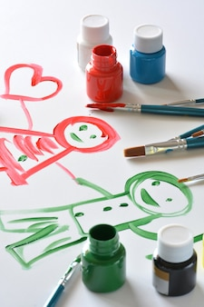 Watercolors and brushes with children's drawings on white canvas