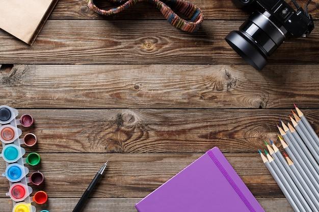Акварели, цветные карандаши и альбом для рисования на деревянном столе. плоские лежал фото с пустым пространством для логотипа, текста.