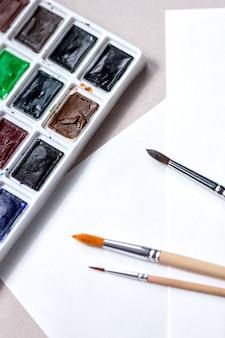 Акварельная палитра с оттенками и кистями для красок на белой стене