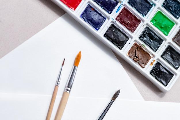 色合いとホワイトペーパーの壁の絵の具のためのブラシの水彩絵の具パレット