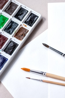 Watercolors palette with tints and brushes for paints on a white paper wall