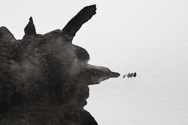 Il nero liquido dell'acquerello spruzza su fondo bianco