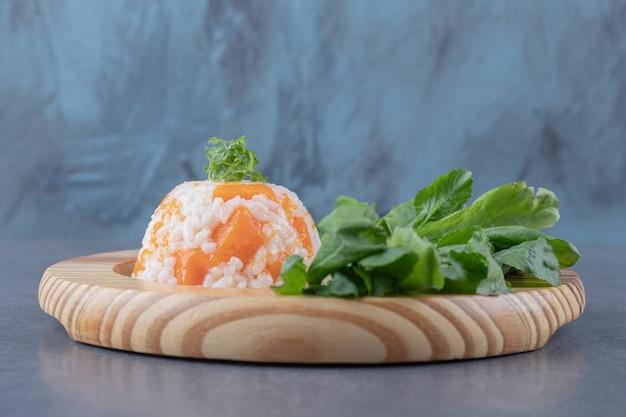 Кресс-салат и рис с морковью на деревянной тарелке, на мраморной поверхности.