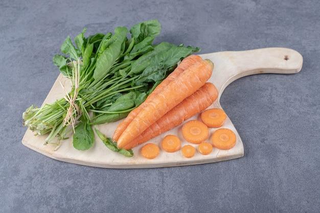 Crescione e carote sul tagliere, sulla superficie di marmo.