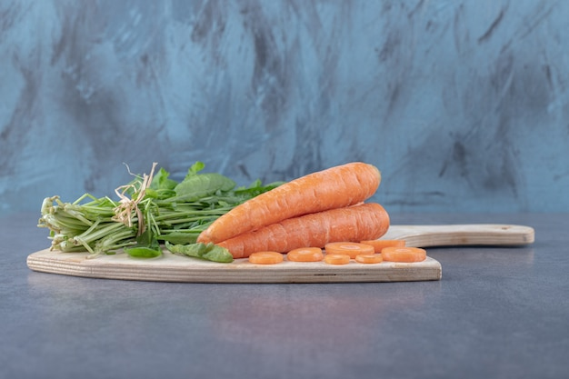 Watercress and carrots on the cutting board , on the marble surface.
