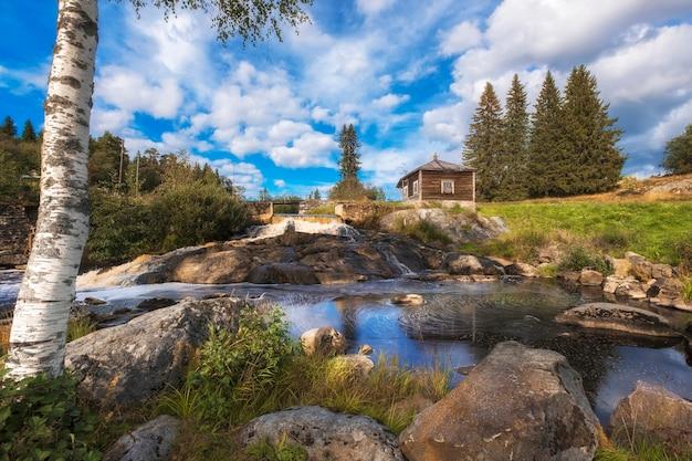 夏の日のカレリアロシアのソスクアの村の古い放棄された発電所の滝