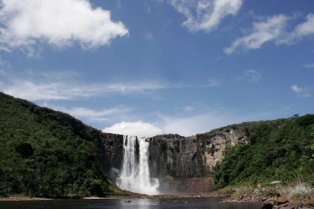 Водопад между горами днем