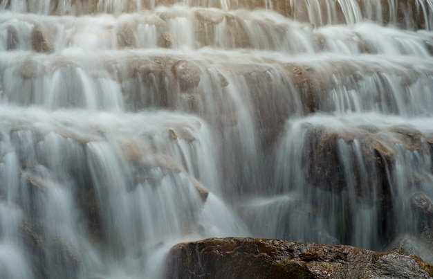 Waterfall flowing into a line of rocks.