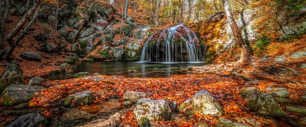 Waterfall in the forest in autumn among the fallen colorful bright leaves.