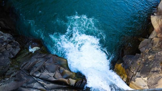 Водопад сверху вниз. вид сверху на ручей, вода течет по камням. каменистый горный водопад. воздушный пейзаж горный каменистый каскад речной ручей естественный живописный фон.
