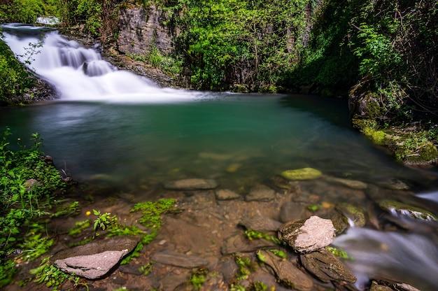 이탈리아 칼바리 근처 리구리아 내륙의 녹색 작은 연못에 있는 폭포