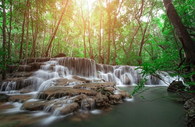 Водопад в тропическом лесу на западе таиланда с оранжевым солнечным светом в фоновом режиме. съемка с медленной скоростью затвора. водопад хуай маэ кхамин, провинция канчанабури.