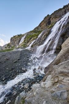 빙하 능선 arkhyz, 소피아 폭포 녹는 코 카 서 스 산맥에 폭포. 순수한 얼음 물의 강 러시아의 아름다운 높은 산. 산에서 여름 하이킹