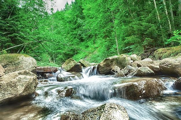 Водопад в горном лесу. красивый фон из камня, воды, мха.