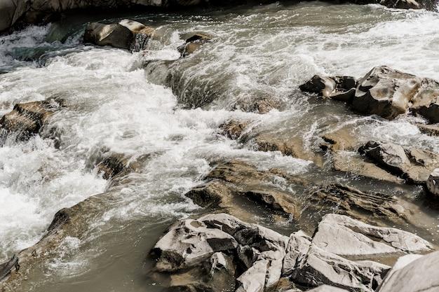 大きな岩のある山の川の滝