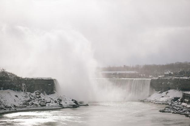 カナダのオンタリオ州のナイアガラフォールズの背景に木がある冬の滝