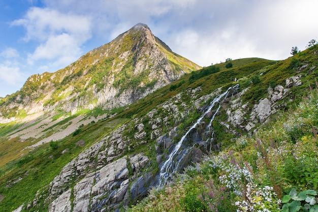 Пейзаж горной долины водопада. горный водопад на фоне деревни горной долины