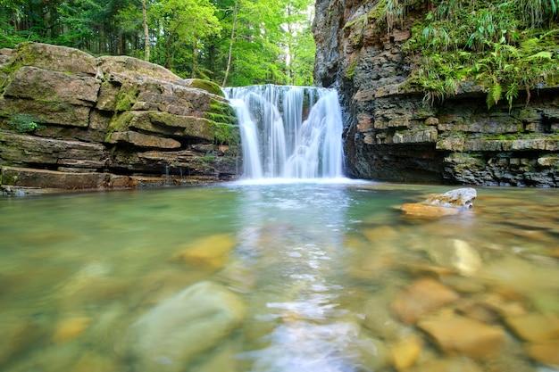 夏の森の岩層から白い泡の水が落ちる山川の滝。