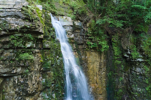 Водопад на горной реке с белой пенистой водой, падающей со скалистого образования в летнем лесу.