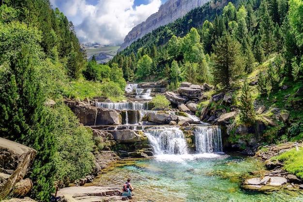 Водопад на ступенях или террасах в зеленом пейзаже между деревьями и горами в ордесе. соасо встает.