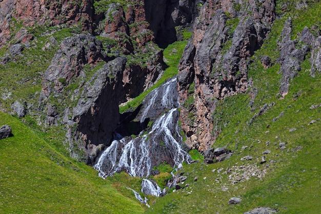 Водопад на каменистых склонах кавказских гор в россии.