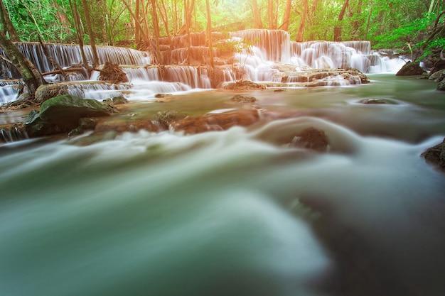 Waterfall in rain forest in west of thailand with orange sun light in background. slow speed shutter shoot. huai mae khamin waterfall, kanchanaburi province.