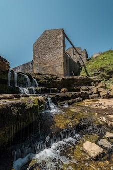 Waterfall of a river with an old ruined mill