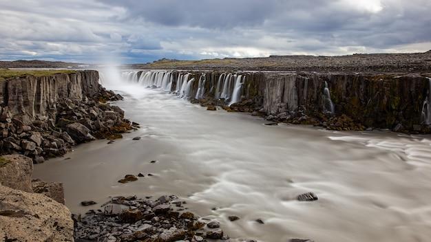 Водопад сельфосс со скалистыми стенами вокруг реки в исландии