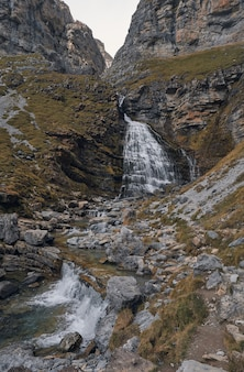 Водопад, который падает между скалами горы