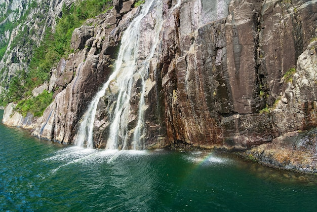 Водопад с радужным видом на море, люсе-фьорд