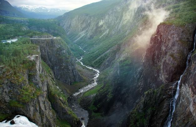 Водопады, стекающие с высокой скалы в глубокую расселину в норвегии.