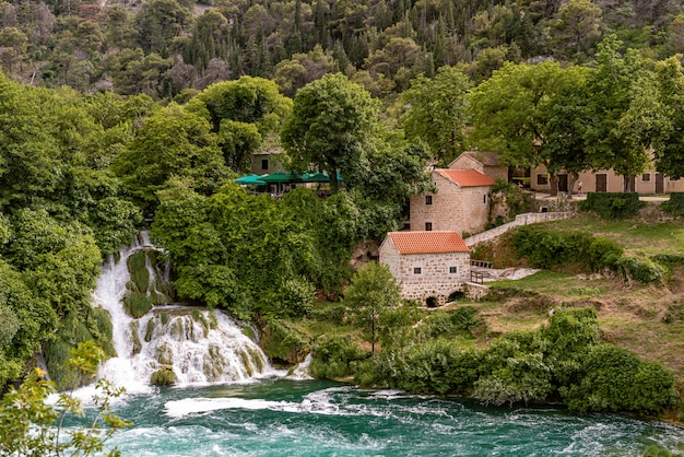 The waterfalls of krka national park and stone mill building with orange tile roof, dalmatia, croatia