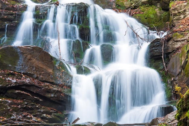 Waterfalls on rocky stream, running through autumn mountain forest