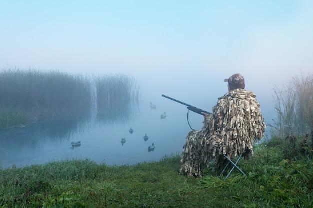 총을 든 물새 사냥꾼. 여름이나 가을 시즌에 오리에 위장 사냥에 사냥꾼.