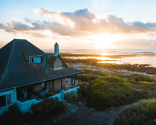 Waterfront house on the beach with a beautiful setting sun in the horizon