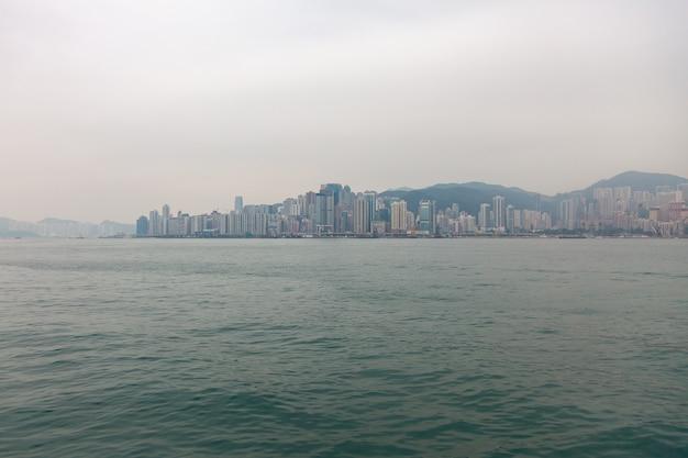 거대 도시의 홍콩 섬에 있는 해안가. 명소와 전망이 있는 큰 아시아 도시의 관광지. 안개에 제방의 도시 풍경입니다.