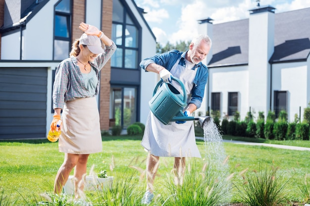Watering bed. husband and wife wearing casual clothes and aprons feeling lovely and happy while watering their garden bed
