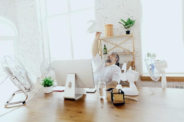 살수. 사업가, 사무실에서 컴퓨터와 팬을 식히는 관리자, 더위를 느끼고 얼굴이 붉어졌습니다. 팬을 사용하지만 여전히 캐비닛의 불편한 기후로 고통 받고 있습니다. 여름, 사무실 작업, 비즈니스.